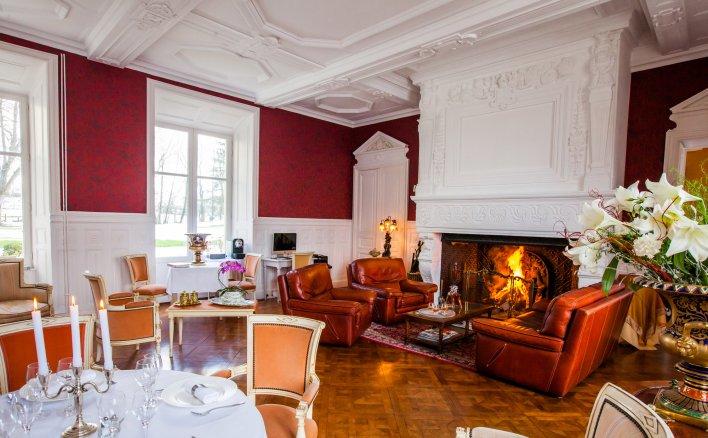 Vaste salle de réception avec fauteuils disposés au coin du feu de cheminée allumé et tables dressées