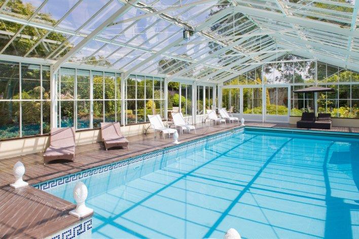 Vaste piscine de nage couverte entourée de fauteuils de détente