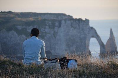 Homme trentenaire accroupi face à la falaise d'Etretat lors du coucher de soleil