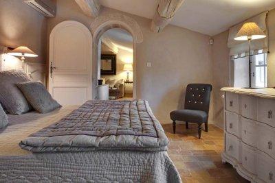 Chambre avec linge de lit gris et poutres apparentes
