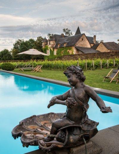 Piscine avec statue de bronze et château en arrière plan