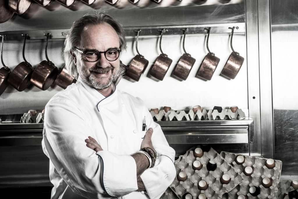 Portrait d'un chef en blouse blanche arrière plan casserole en cuivre