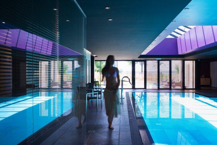 Salle de spa avec piscine couverte et jeune femme marchant au bord de l'eau