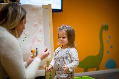 Petite fille en train de sourire face à une baby-sitter lui faisant choisir des feutres pour s'amuser