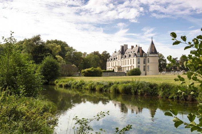 Château entouré de végétation d'un plan d'eau