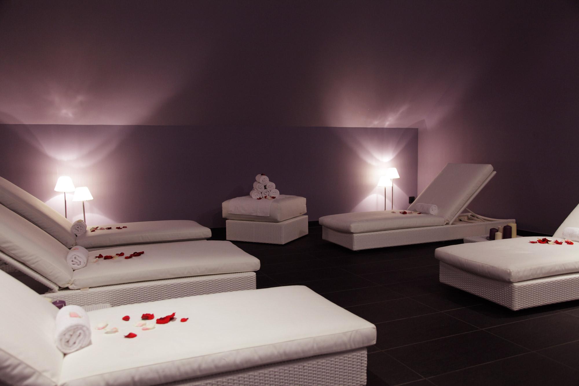 Salle de soins spa équipée de tables de massage parsemées de pétales de roses dans une ambiance tamisée