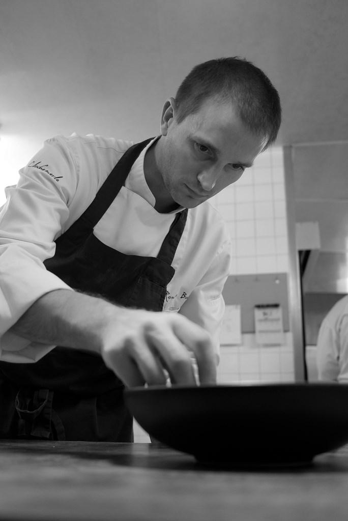 photo noir et blanc d'un cuisinier disposant des aliments dans une assiette