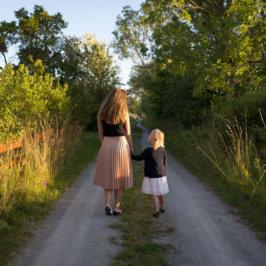 Maman et sa petite fille de dos en train de se balader sur un chemin de campagne