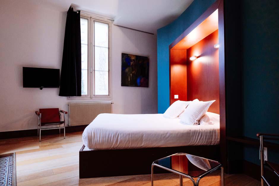 Chambre lit double tête de lit encadré rouge et bleu
