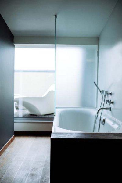 Salle de bain avec baignoire blanche et vitre verre givré
