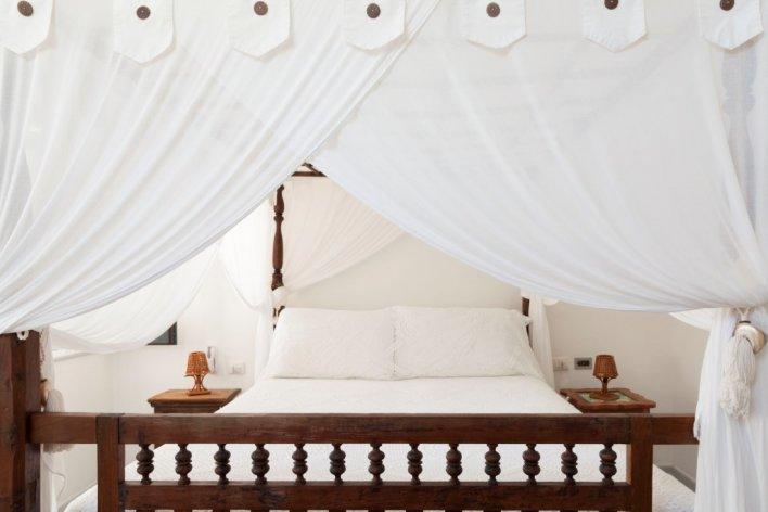 Chambre lit double à baldaquin linge de lit blanc et cadre de lit en bois