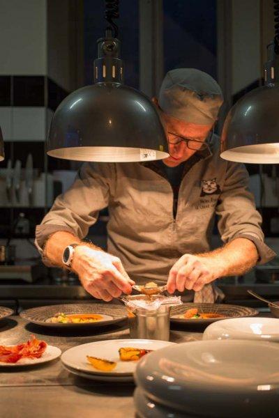 chef en tenue de cuisine manipulant ses ingrédients