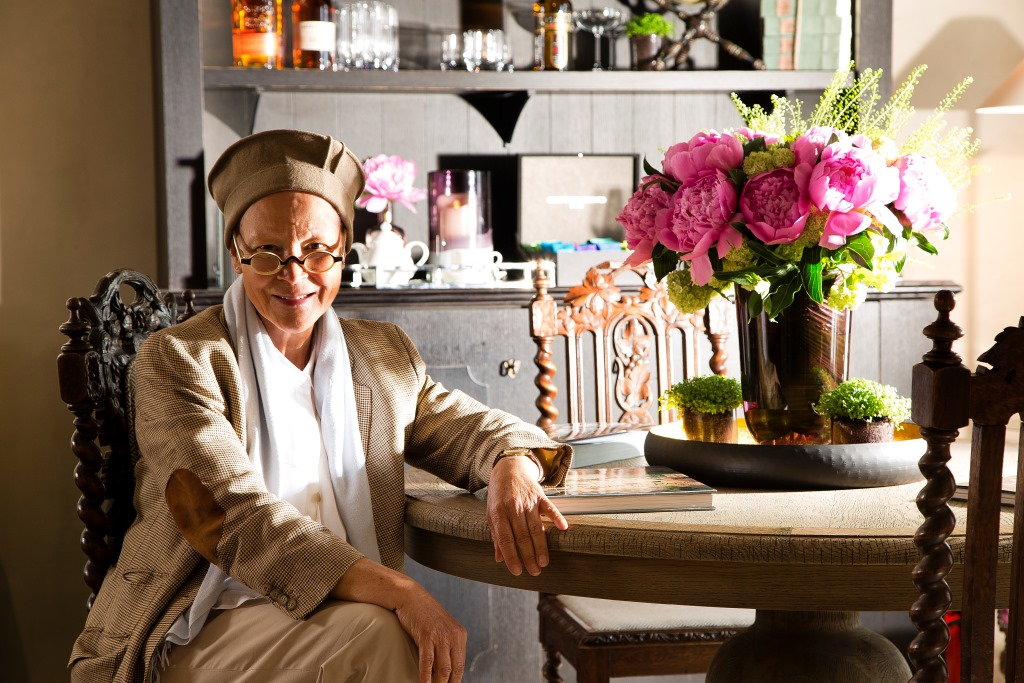 Femme accoudée à une table avec un vase rempli de fleurs roses