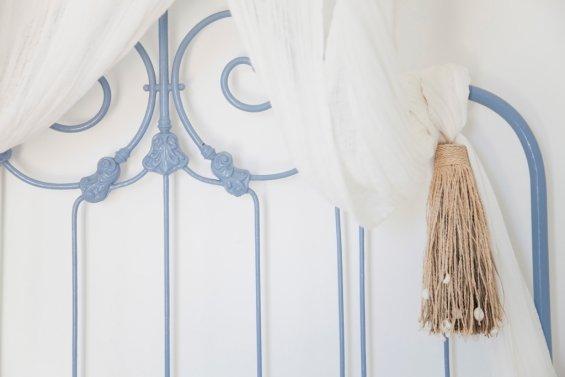 zoom tête de lit fer forgé bleu ciel et rideau blanc