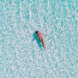 Jeune femme en maillot de bain 2 pièces en train de flotter sur le dos dans une piscine