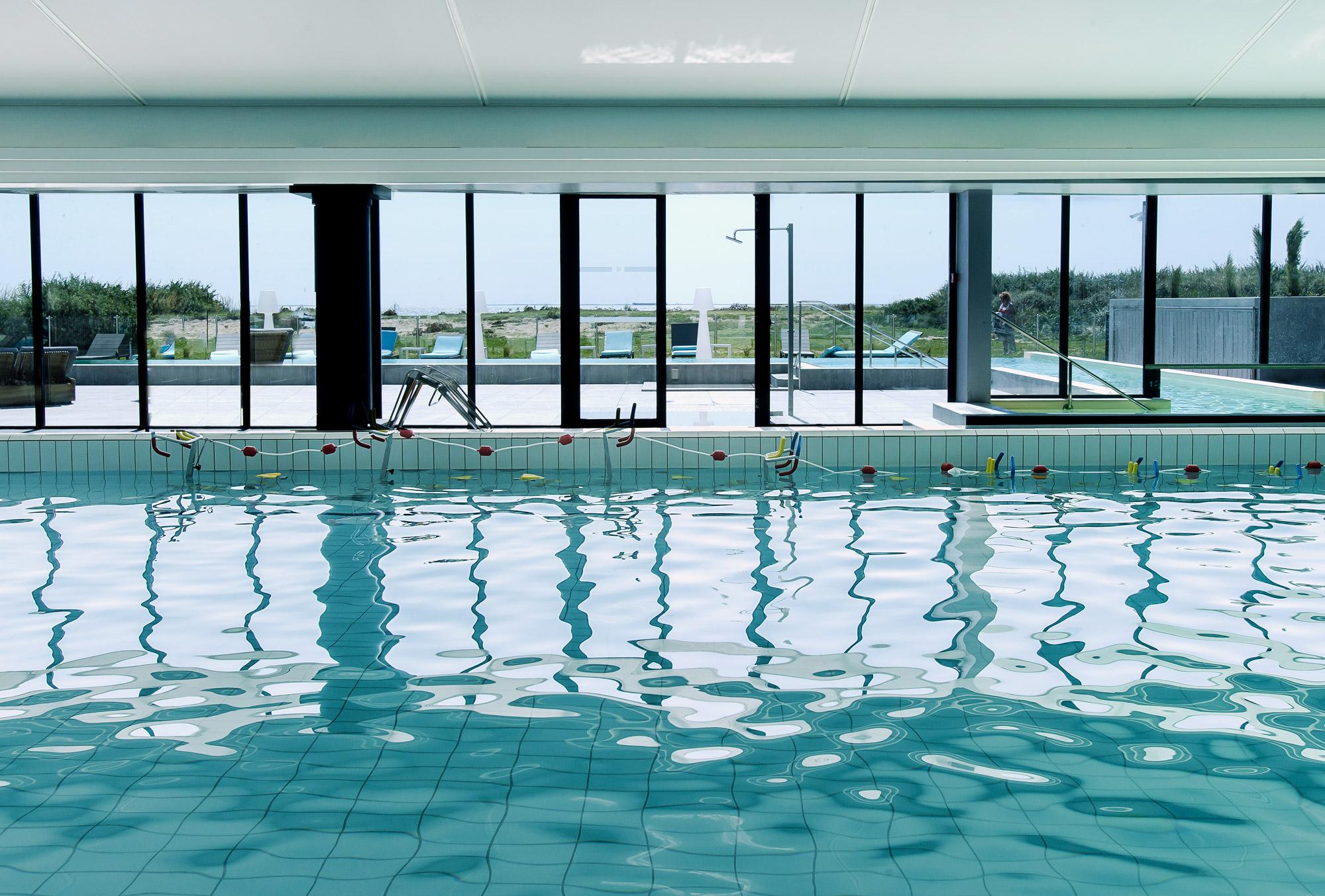 Vaste piscine intérieure avec baie vitrée accédant sur une terrasse extérieure