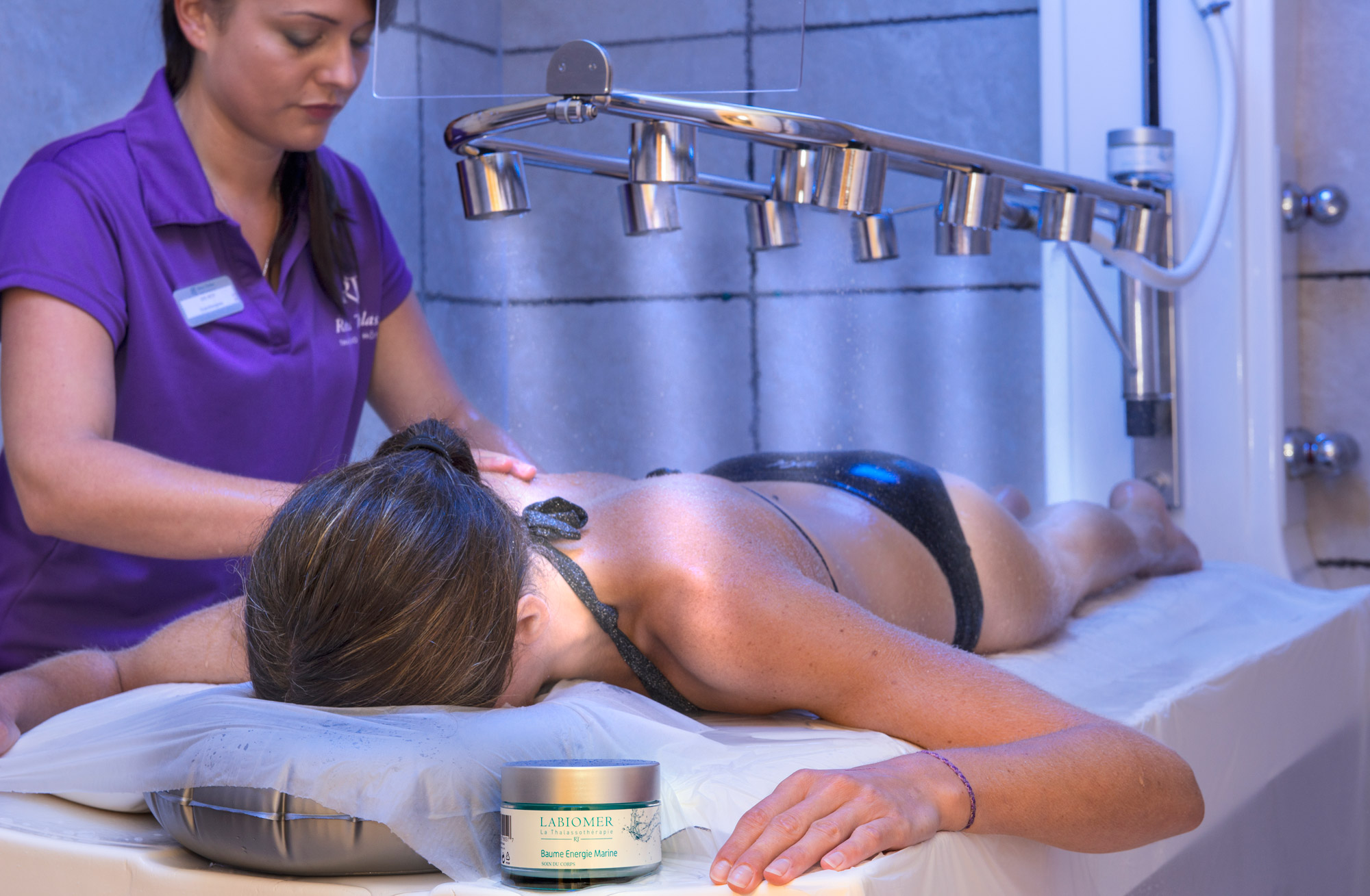 Jeune femme allongée sur une table de massage en train de profiter de soins thalasso