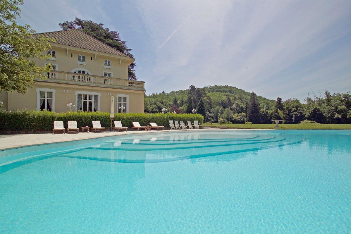 Immense piscine extérieure entourée d'une terrasse carrelée ameublée de transats et chaises longues