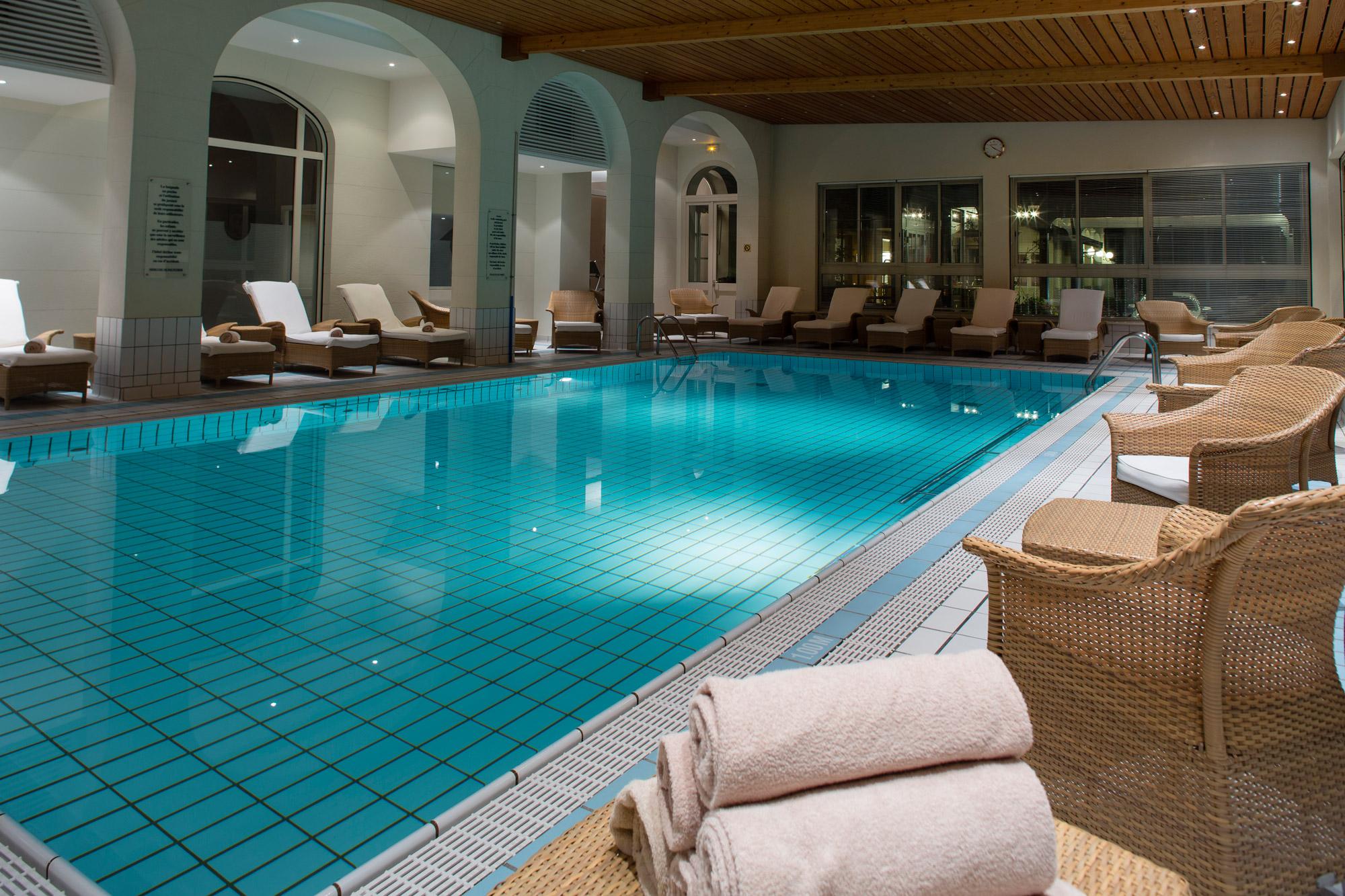 Vaste piscine intérieure entourée de tranats et de fauteuils pour se relaxer.