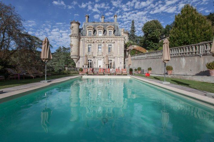 Grande piscine extérieure entourée de transats de relaxation avec vue sur la façade historique de l'hôtel.