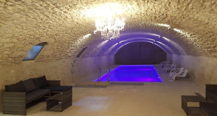 Piscine intérieure installée dans une cave voûtée, surplombée d'un lustre, avec canapés tout autour pour se relaxer.