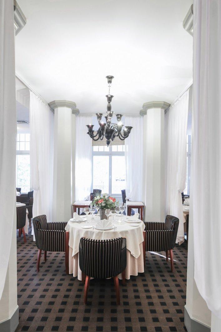 Aperçu d'une salle de restaurant avec tables dressées dans un cadre chic avec colonnes, drapés et lustres.
