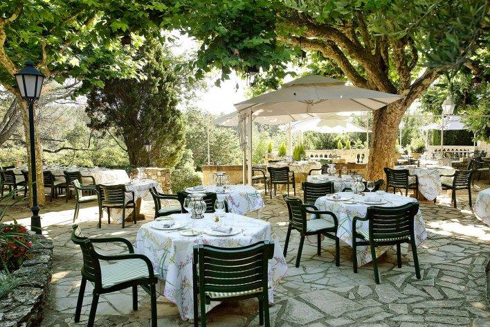 Terrasse provençale avec tables dressées à l'ombre du feuillage.