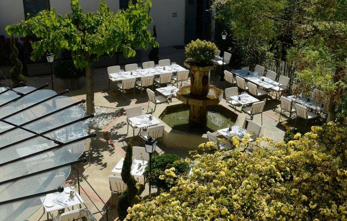 Terrasse provençale avec fontaine centrale et tables pour déjeuner tout autour.