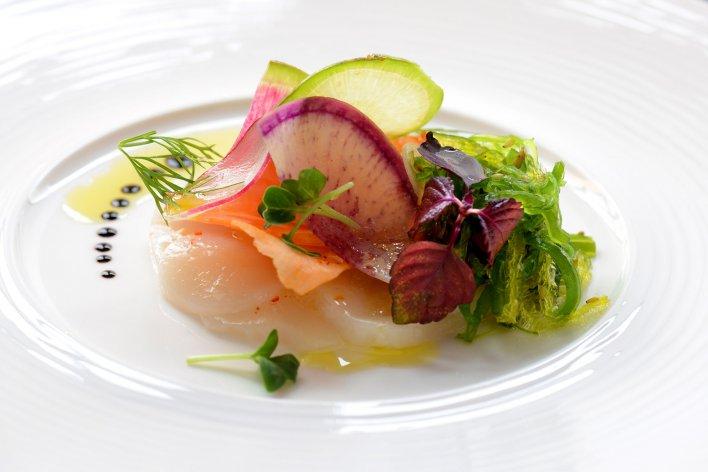 Plat à base de légumes et noix de Saint-Jacques dressé à la manière d'un restaurant gastronomique.