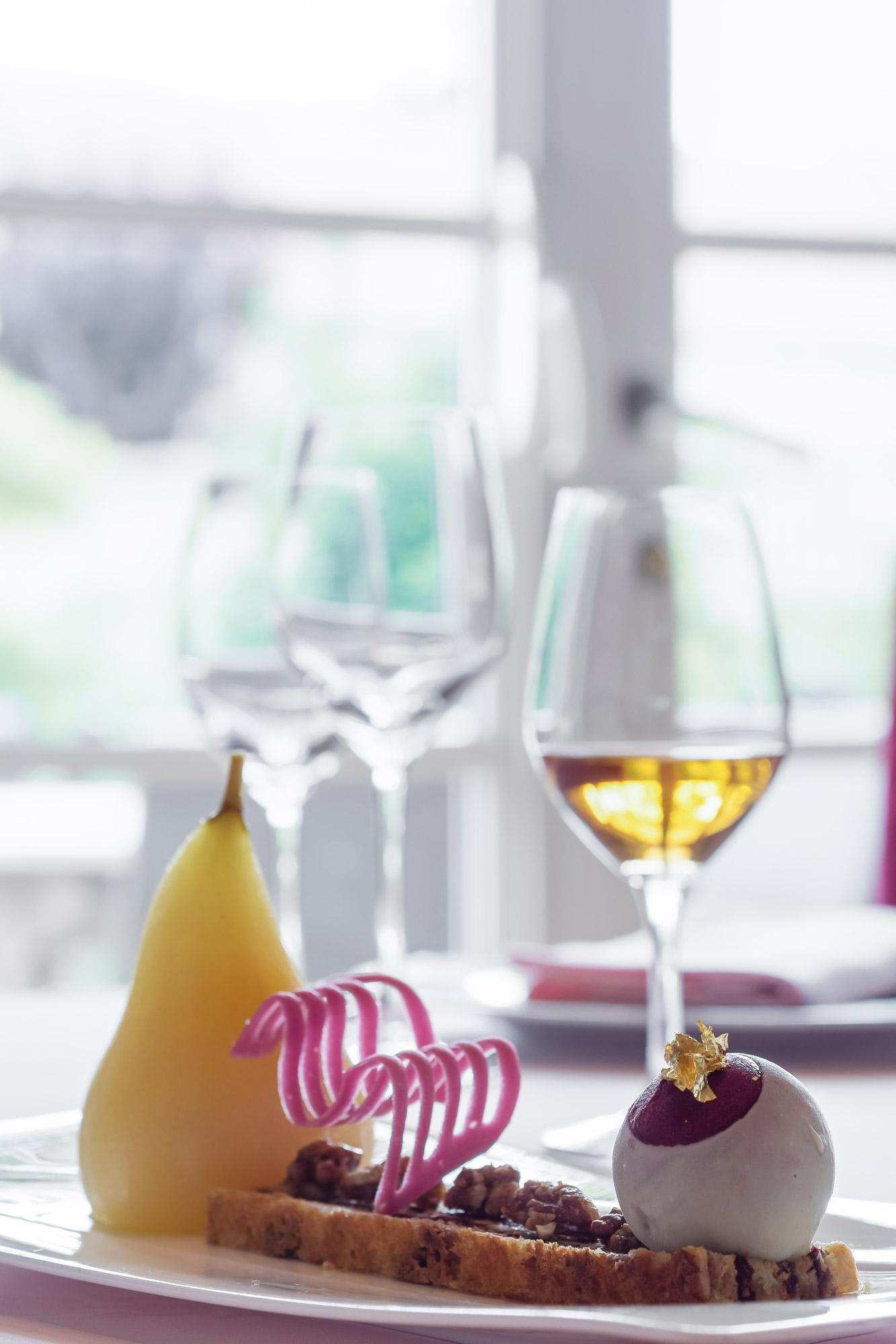 Dessert réalisé dans un restaurant gastronomique à base de poire et de glace accompagné d'un verre de vin blanc.