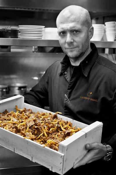 Portrait du chef Laurent Rigal tenant une caisse remplie de champignons.