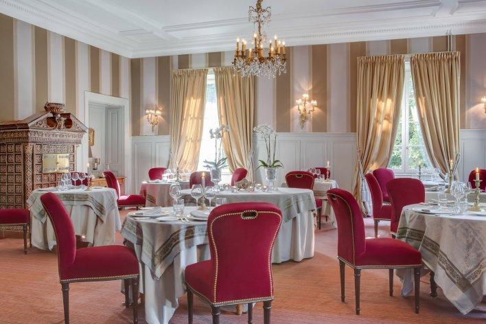 Salle de restaurant chic décoré avec des tentureset des fauteuils en velours rouge.