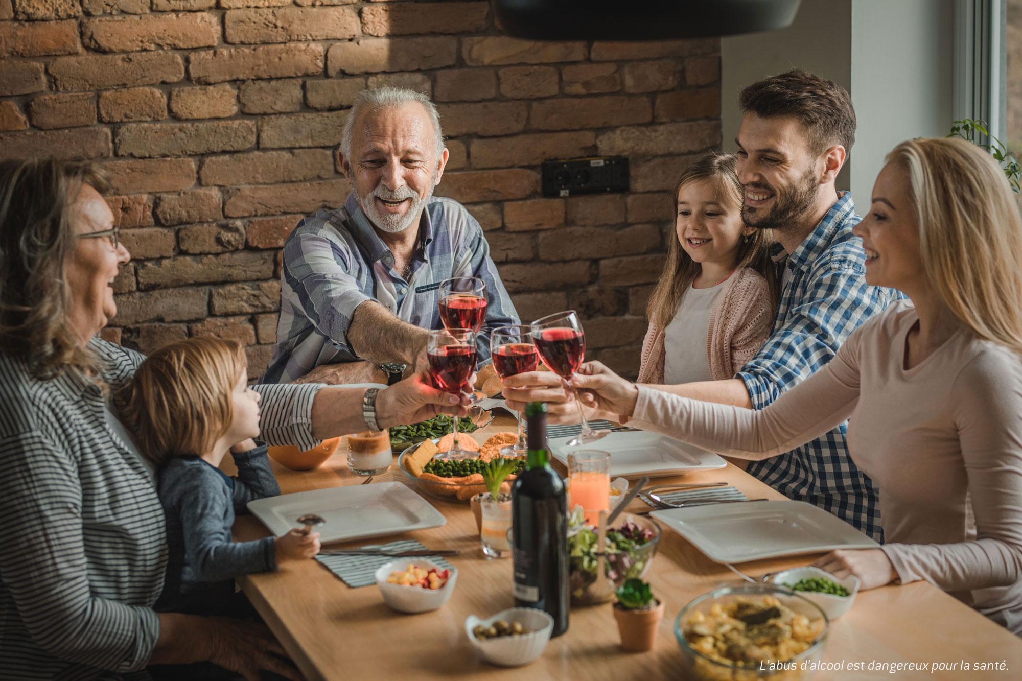 Famille en train de déjeuner et de trinquer tous ensemble à table.