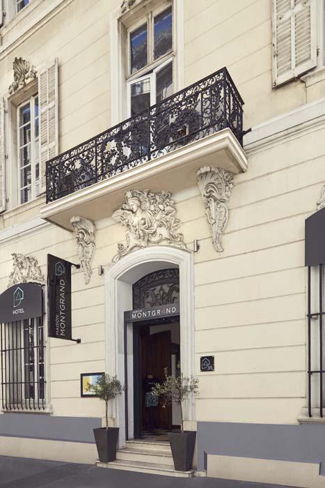 Façade hôtel pierre blanche et balcon forgé noir