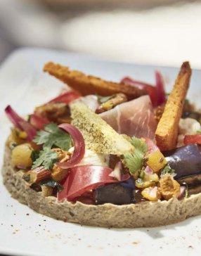 Plat de légumes et jambon cru disposé en cercle dans une assiette blanche