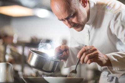 Photo d'un chef tenant une casserole dans une main et une cuillère dans l'autre pour dresser un plat