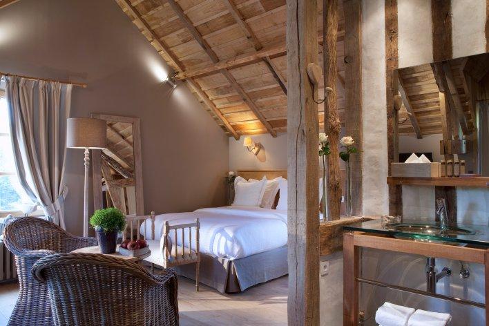 Chambre d'hôtel romantique décorée de meubles en bois pour passer un agréable week-end.
