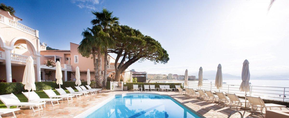 Paysage côtier de Corse, avec vaste piscine extérieure entourée de transats et de parasols.