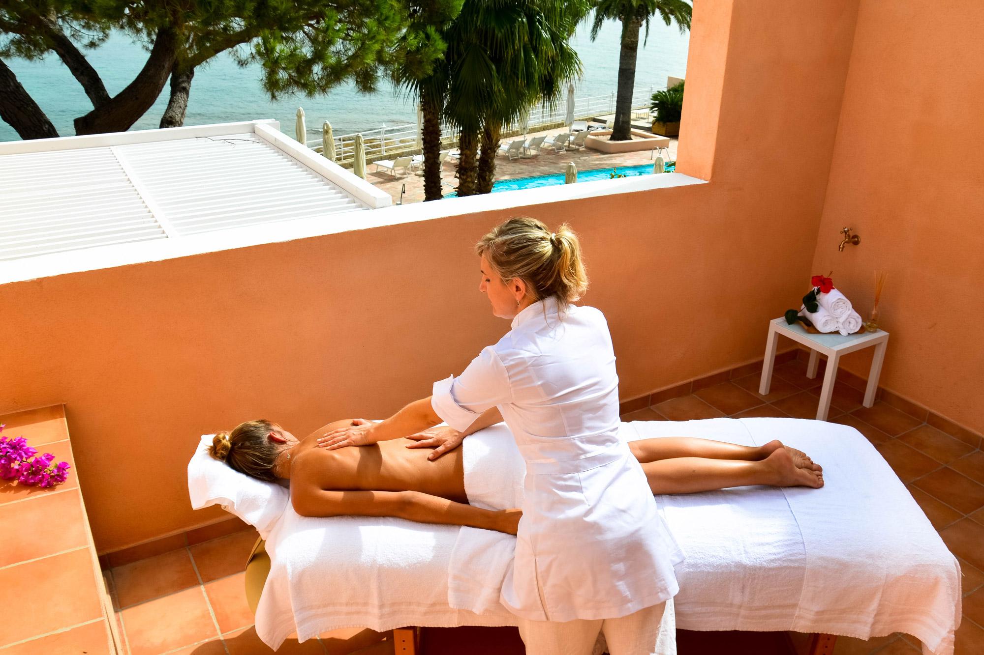 Jeune femme installée sur une table de massage sur un balcon de chambre d'hôtel, en train de recevoir un soin.