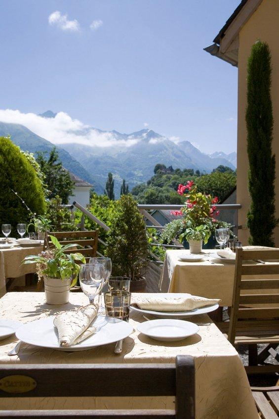 Table dressée en terrasse avec vue imprenable sur la montagne par temps ensoleillé.