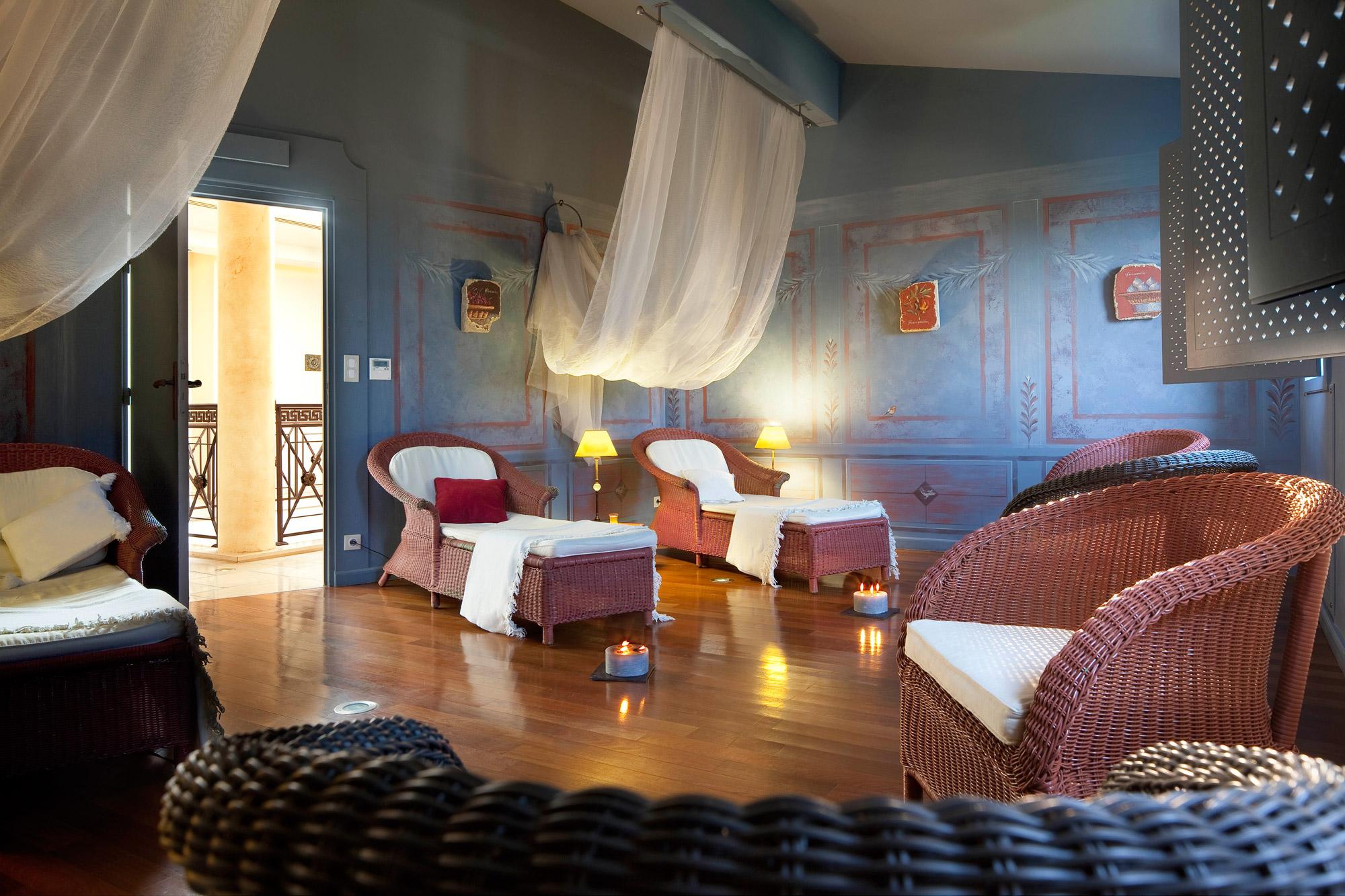 Grande salle dédiée aux soins et à la détente dans une ambiance feutrée et cocooning, meublée de fauteuils de relaxation en osier.