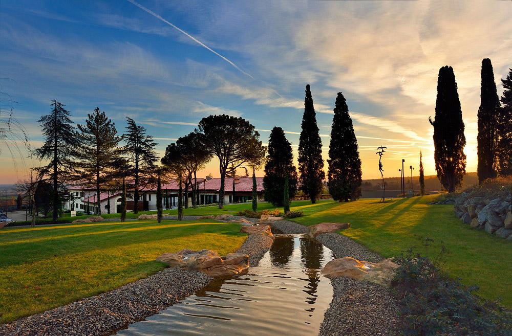 Vaste parc arboré en Italie avec cours d'eau traversant la propriété au coucher du soleil.