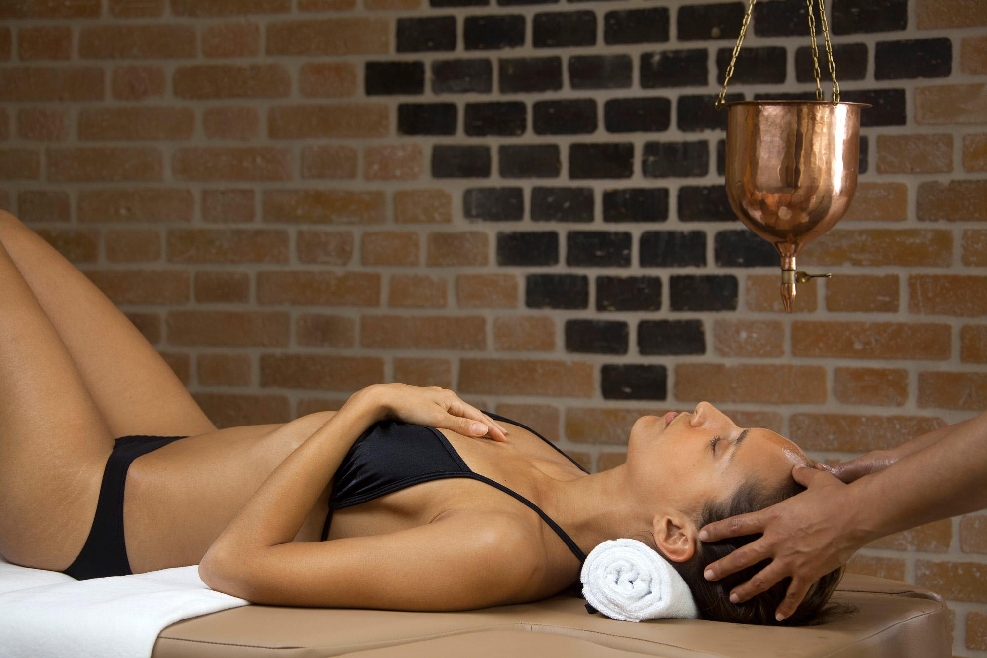 Jeune femme en maillot de bain installée sur le dos, en train de se faire masser le sommet de la tête.
