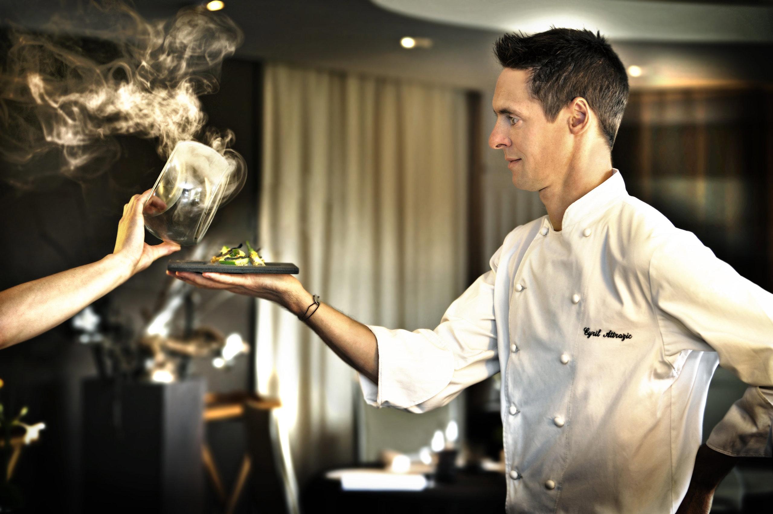 Chef en veste de cuisine de profil avec un plat dans la main