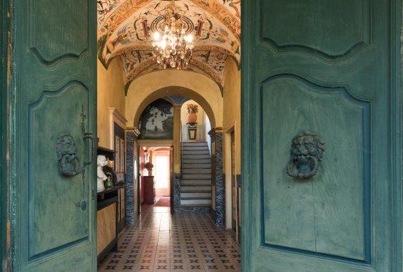 porte d'entrée bleu ouvrant sur couloir jaune avec fresque