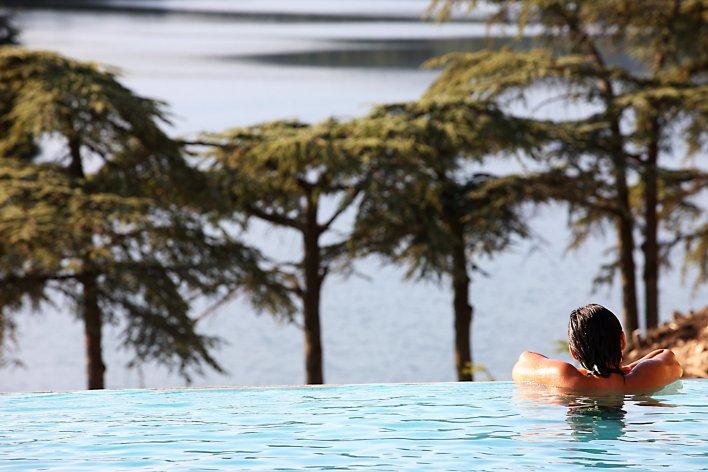 Piscine à débordement avec femme sur le rebord dans la piscine
