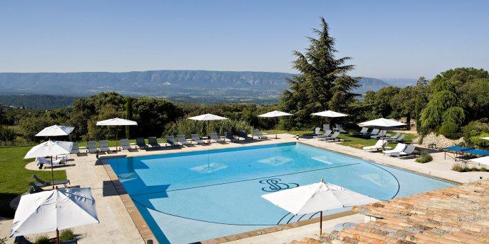 VAste piscine extérieure entourée de transats avec vue sur les montagnes.