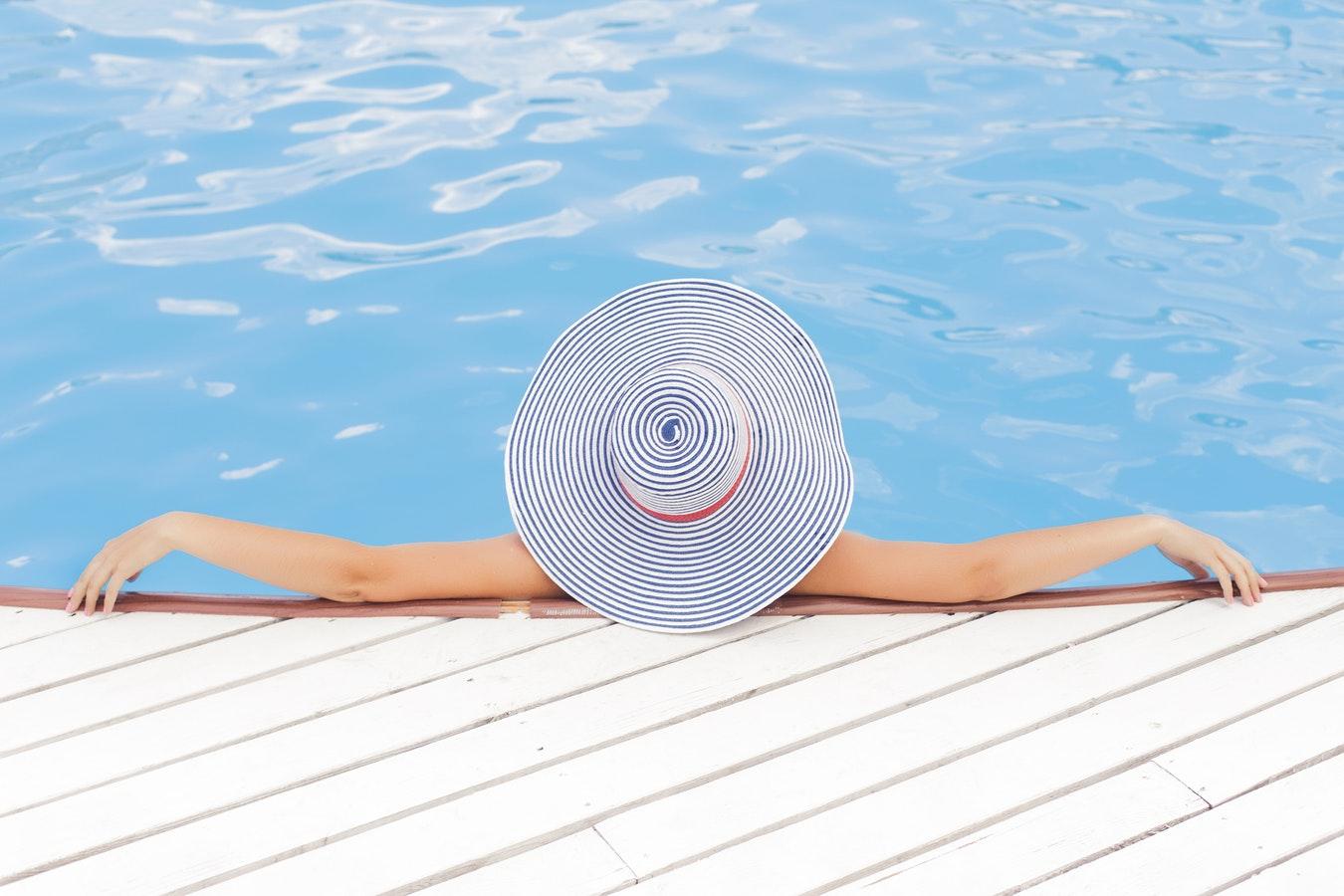 Femme dans piscine avec chapeau