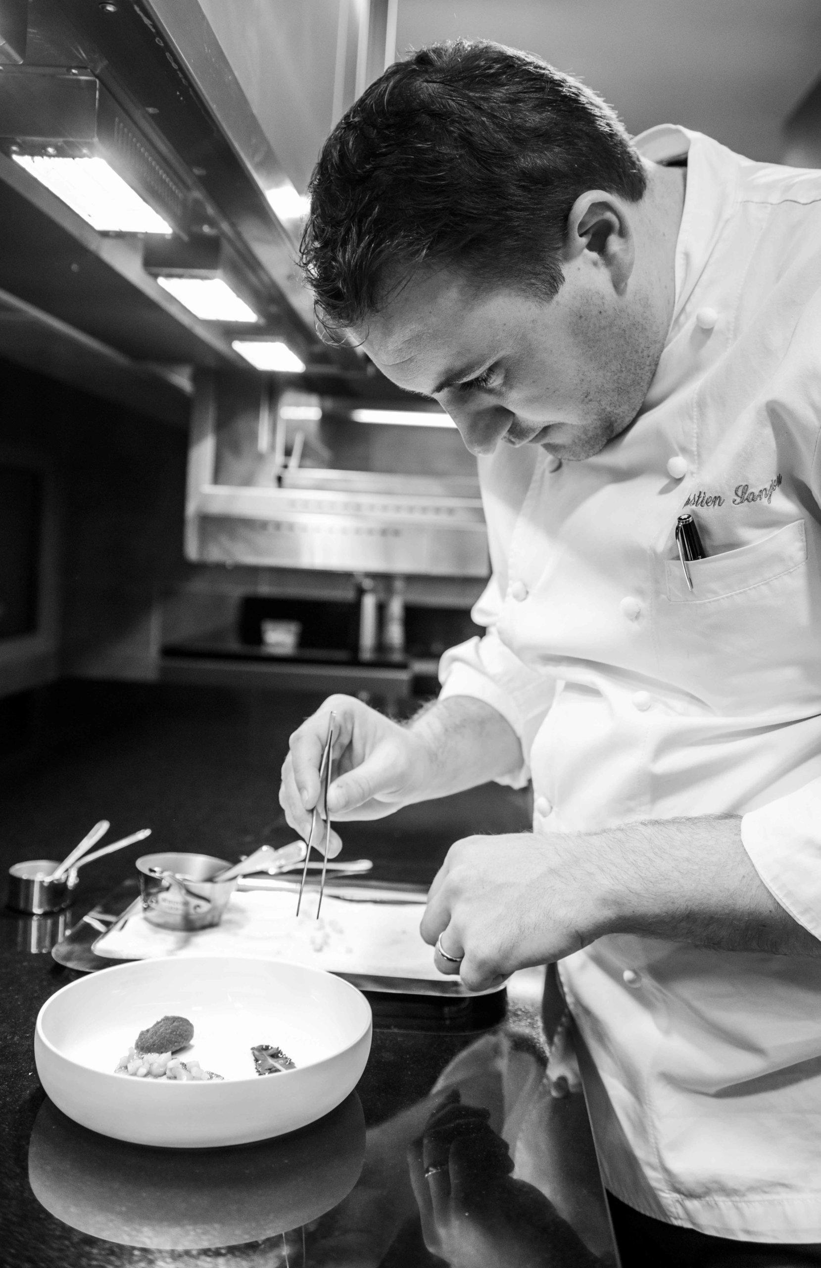 Chef en veste dans sa cuisine prépare un plat
