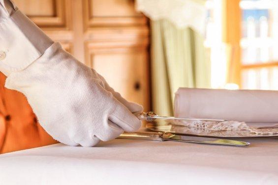 main avec gant blanc pour dresser une table